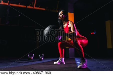 Sportswoman Doing Squat Exercises With Fitness Ball. Female Exercising And Stretching With Medicine