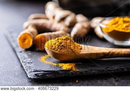 Indian turmeric powder and root. Turmeric spice. Ground turmeric in wooden spoon.