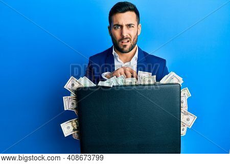 Young hispanic businessman holding briefcase full of dollars clueless and confused expression. doubt concept.