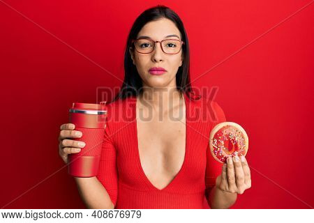Young latin woman eating doughnut and drinking coffee relaxed with serious expression on face. simple and natural looking at the camera.