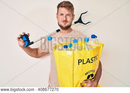 Young caucasian man holding recycling bag with plastic bottles and waste picker puffing cheeks with funny face. mouth inflated with air, catching air.
