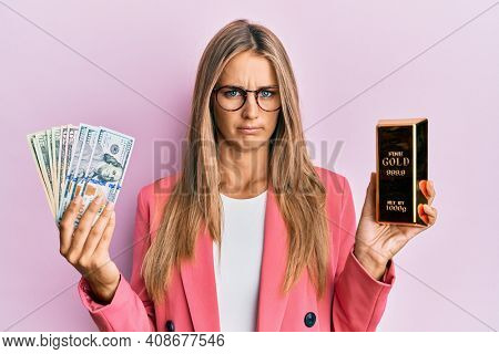 Young blonde woman wearing business style holding gold ingot and dollars skeptic and nervous, frowning upset because of problem. negative person.