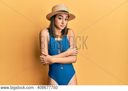 Young brunette girl wearing swimsuit and summer hat shaking and freezing for winter cold with sad and shock expression on face