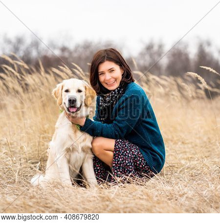 Cheerful woman with devoted dog in early spring nature