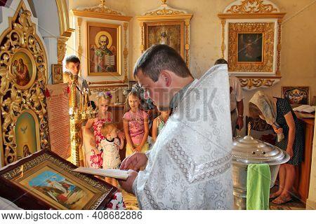 Chernihiv - Ukraine.  2 July 2014: Priest Conducting Ceremony Of Baptizing Child. Priest Reading Pra