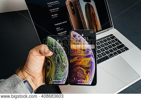 Paris, France - Sep 25, 2018: Pov Male Hand Holding Compare Two New Latest Smartphones By Apple Comp