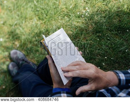 Paris, France - May 3, 2020: Overhead View Of Curious Senior Male Reading The Book Rich Dad Poor Dad