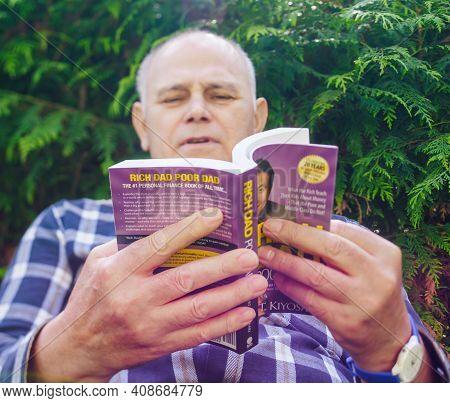 Paris, France - May 3, 2020: Low Angle View Of Curious Senior Male Reading The Book Rich Dad Poor Da
