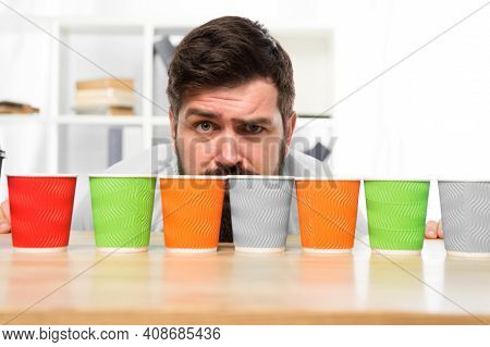 Difficult Choice. Decision-making. Serious And Sad Man With Colorful Coffee Cups. Many Cups Of Coffe