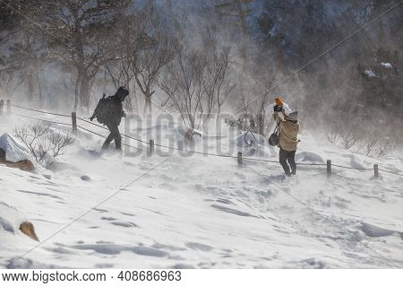 Snowstorm At The Top Of The Mountain. Two People Stand In A Strong Blizzard On A Mountain Against Th