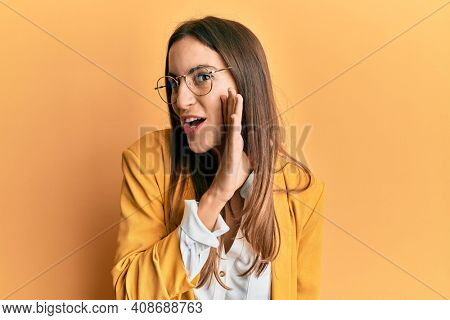 Young beautiful woman wearing business style and glasses hand on mouth telling secret rumor, whispering malicious talk conversation