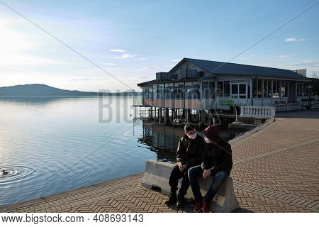 Two Friends Chat In Front Of A Chalet On The Lake With The Anti-covid19 Mask. High Quality Photo