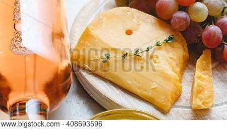 Aged Dutch Gouda Cheese On Cheeseboard With Cumin Herbs On Table. Cheddar Cheese With Grapes, Pink W