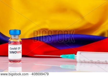 Bogota, Colombia - February 2021. Sinovac Covid Vaccine Vial And Colombian Flag. Vaccination Concept
