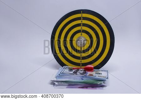 Concept Of Success And Goal Achievement. Round Dart Board With A Bundle Of Dollars, Euros And A Bitc