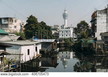 Scene Of Pak Nam Observation Tower And Surrounding Homes In Pak Nam, Thailand, With Water In Foregro