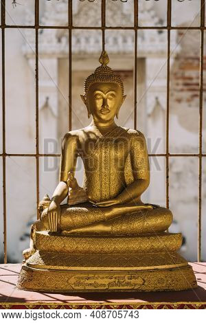 Golden Sitting Buddha Statue With Sun Shining On It In Thailand.