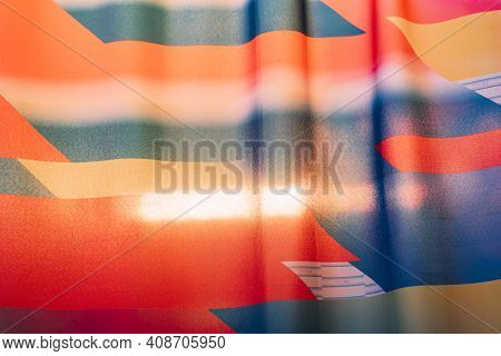 Thin, Shining Cloth Sheet With Neon, Red, Blue And Yellow Color With Light Shining From Behind.