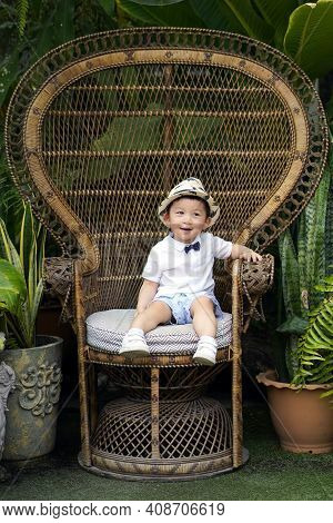 A Cute Boy Wearing A White Shirt And Dressed In Vintage Casual Look. A Cute Dressed Little Child Sit