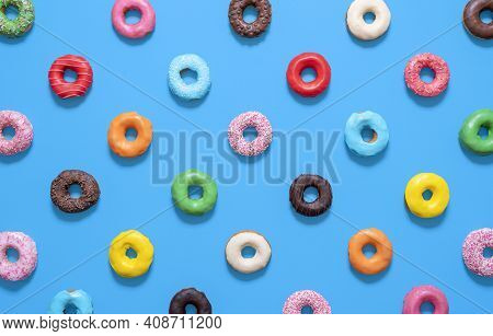Flat Lay With Multicolored Glazed Doughnuts Isolated On A Blue Background. Homemade Chocolate Doughn