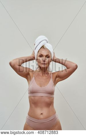 Waist-up Photo Of A Confident Woman In Bikini Placing Both Hands On A Head Towel And Tying It Up. Co