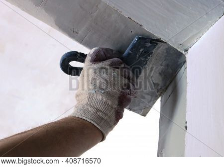 Leveling The Upper Corner Of The Doorway With The Hand Of A Professional In A Glove Holding A Trowel