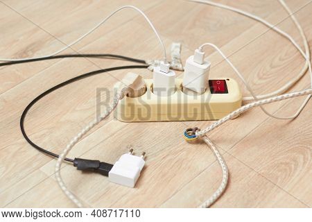 The Extension Cord And Iron Are Lying On The Floor With A Large Current Consumption. The Concept Of