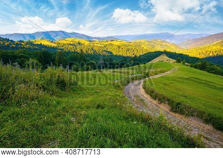 Rural Landscape In Mountains At Summer Sunrise. Country Road Through Grassy Pasture Winding Down In