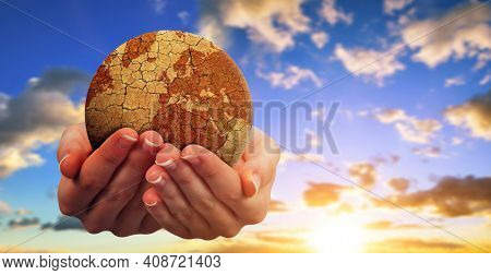 Parched planet earth in hands with sunset sky at the background. Global warming or change climate concept. Environmental problems.