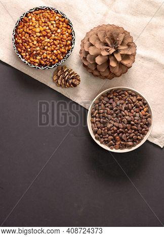 Two Curly Bowls With Peeled Pine Nuts And Nuts, Two Pine Cones On A Linen Cloth And A Black Table. T