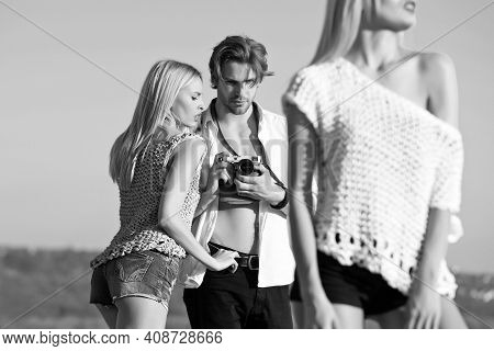 Fashion Model On Photoshoot. Handsome Man Photographer Shooting Sexy Women. Fashionable Models Outdo