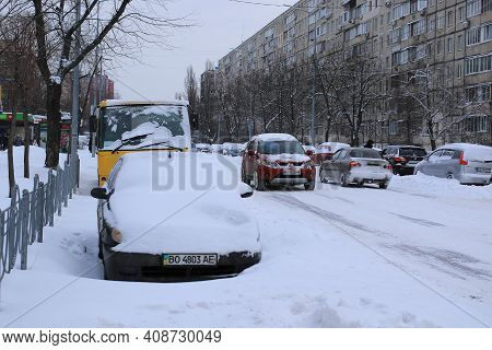 Kyiv Ukraine - February 09 2021: Snowstorm, Snow-covered Street In The City And Cars. Cars Covered W