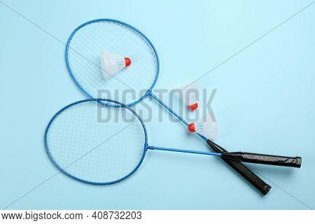 Rackets And Shuttlecocks On Light Blue Background, Flat Lay. Badminton Equipment