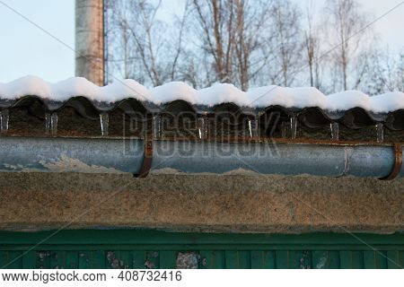 The Water Running Down The Roof Of The Garage To The Gutter Froze, Forming Icicles.it Is The Turn Of