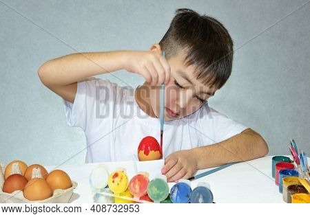 A Boy With A Paintbrush Paints An Easter Egg. Preparing For Easter.