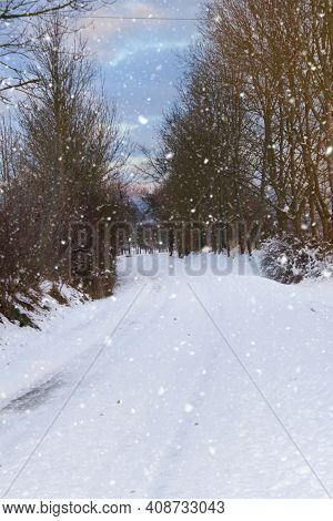 Snowy Road Between Trees. Endless Snowstorms Can Interrupt Traffic.it Snows And Freezes A Lot. The R