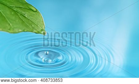 Blue water drop with green leaf, macro shot