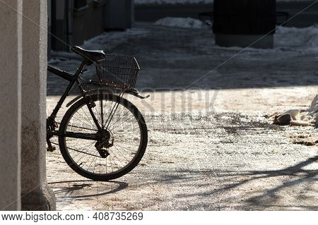 Bicycle On The Street On A Sunny Winter Day At The Wall Of The House