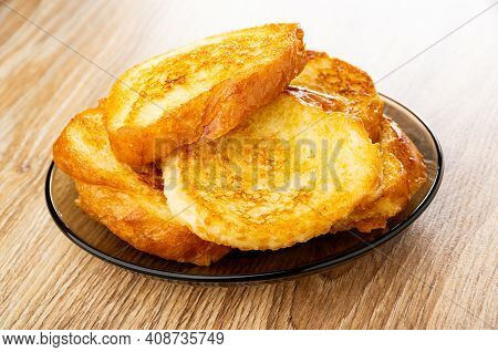 Fried Toasts From Wheat Bread In Brown Transparent Saucer On Wooden Table