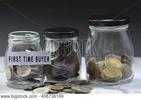 Glass Jars With Multicurrency Coins And Text - First Time Buyer. Home Buyer Concept