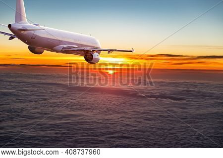 Commercial airplane jetliner flying above dramatic clouds in beautiful light. Travel concept.