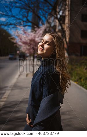 Sakura Branches With Flowers On A Tree On The City Streets. Stylish Woman Girl Runs On The Street Wi