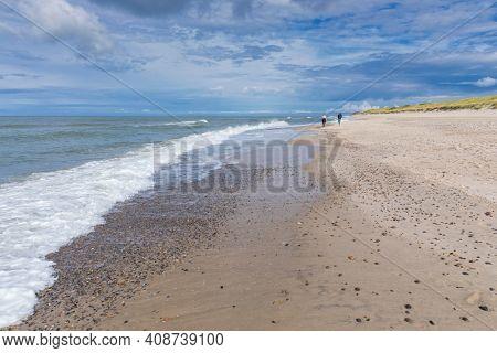 Two unrecognizable persons strolling along the beach  of Bjerregard on the Danish North Sea coast