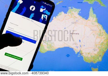Kathmandu, Nepal - February 18 2021: Smartphone With Facebook's Login Screen Against The Maps Of Aus