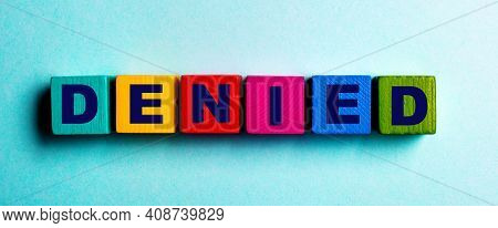 The Word Denied Is Written On Multicolored Bright Wooden Cubes On A Light Blue Background