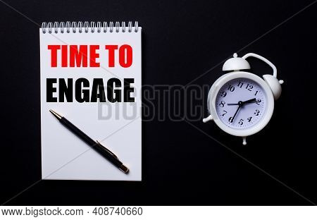 Time To Engage Is Written In A White Notepad Near A White Alarm Clock On A Black Background.