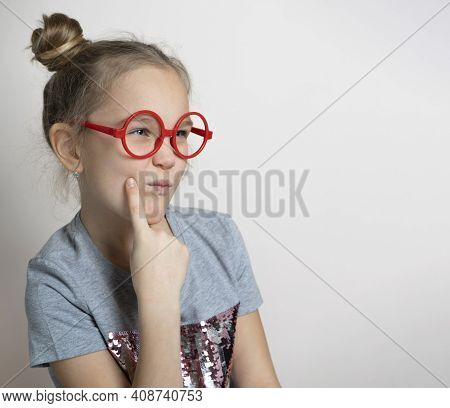 Cute Funny Little Girl With Sly Squint Facial Emotion Wearing Red Toy Eyeglasses Studio Headshot Por