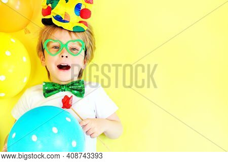 Funny Laughing Child Clown On Yellow Background With Multicolored Balloons, Copy Space. April Fools