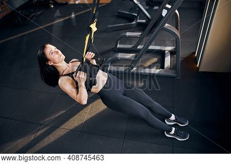 Cheerful Slim Woman Doing Suspension Workout In Gym