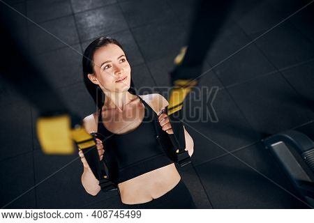 Smiling Young Woman Doing Suspension Training Indoors